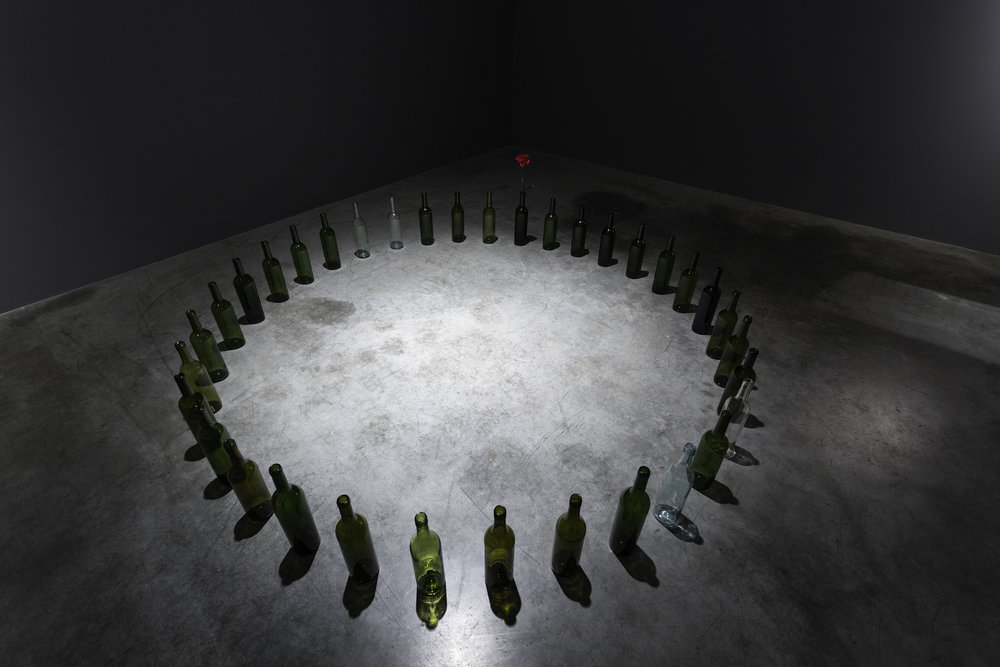 Marco Godinho  Every Day a Revolution  2012 Wine bottles, red carnation flowers Dimensions variable