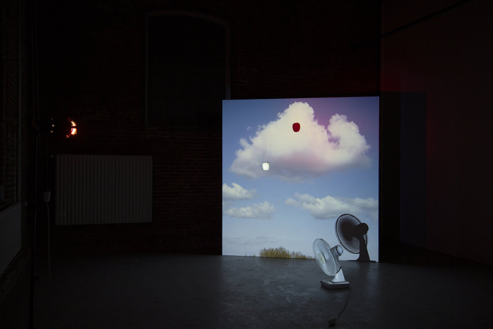 Iqra Tanveer  Meeting the universe halfway 2017 Image projection, plastic apple, wooden screen, red spotlight, pedestal fan 222.5 x 228 cm (screen size)