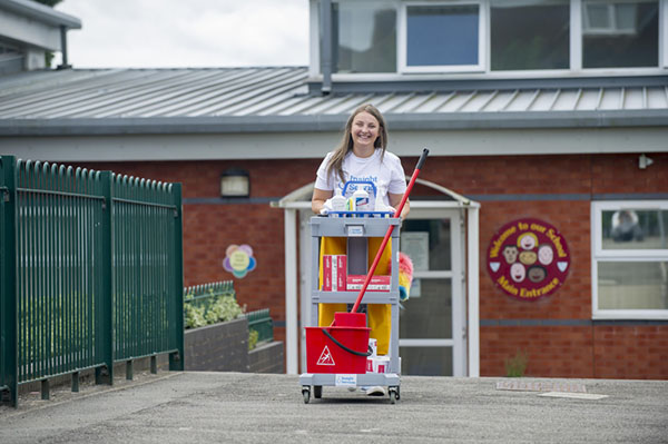 Pushing cleaning cart across school playground