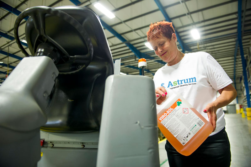 Astrum pouring specialist cleaning fluids into floor cleaning machine