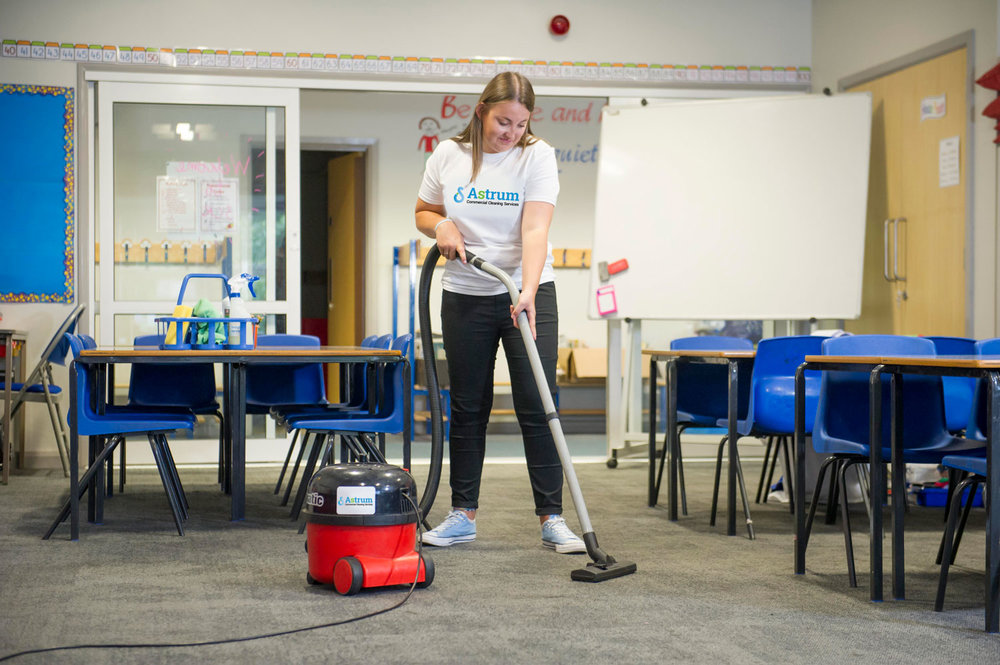 Astrum personnel vacuuming school carpets