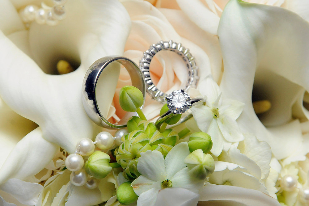 Wedding bands lay together on a beautiful bridal bouquet