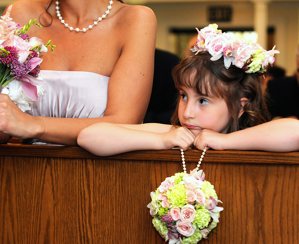 Flower girl and bride at a wedding with luxurious floral arrangements from Bouquets & Beyond