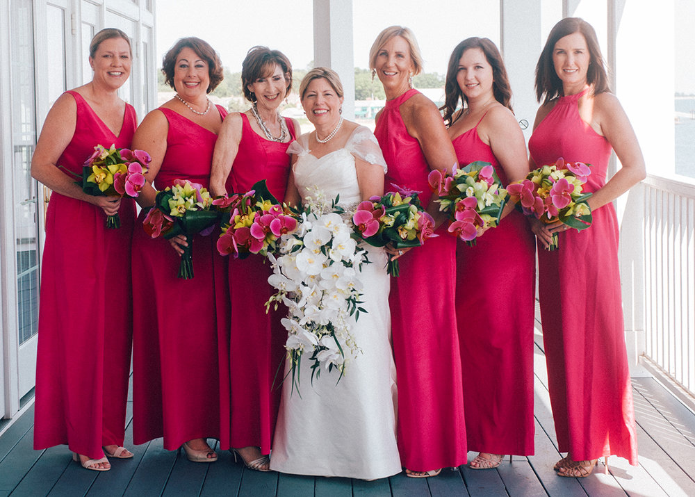 Bride and pink-dressed bridesmaids hold elegant bouquet of orchids and other flowers