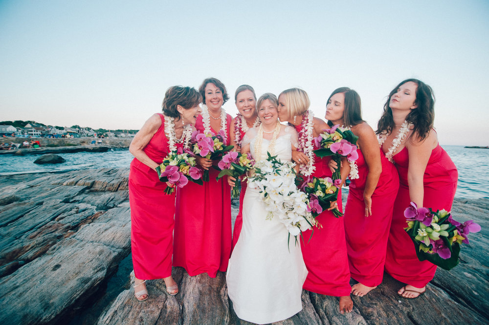 Bride and her bridesmaids holding their bouquets by the water
