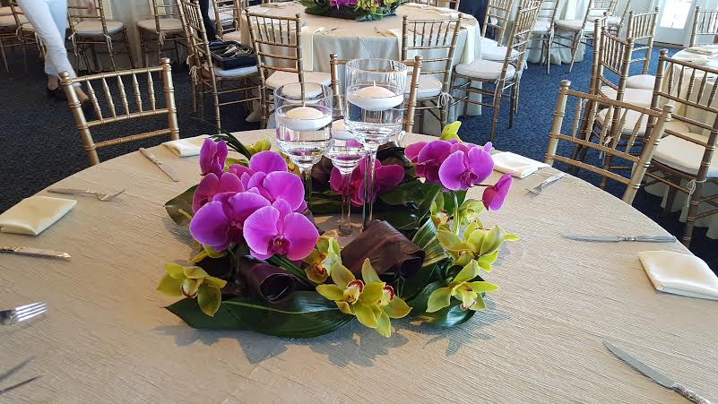 Wedding table centerpiece of elegant purple orchids