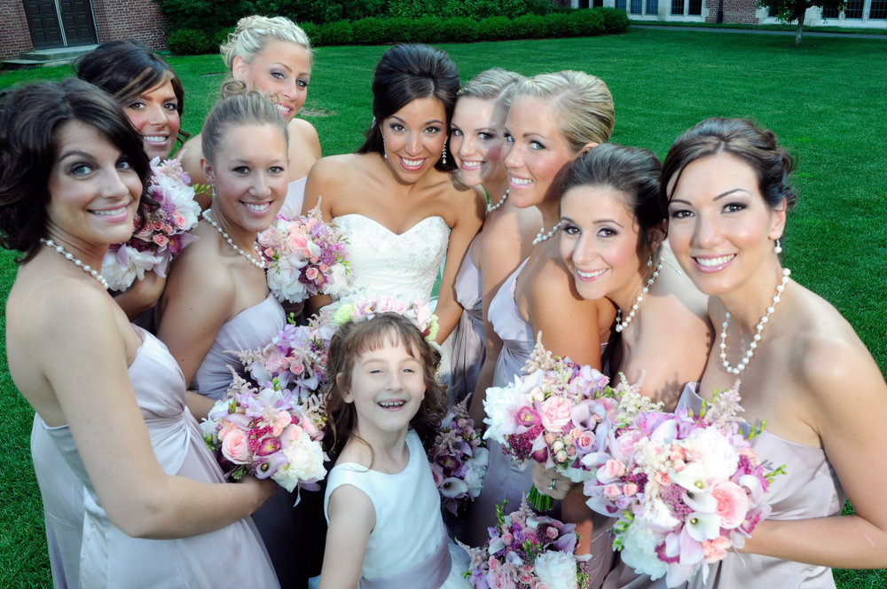 Bride, bridesmaids and the flower girl with pinkish floral arrangements