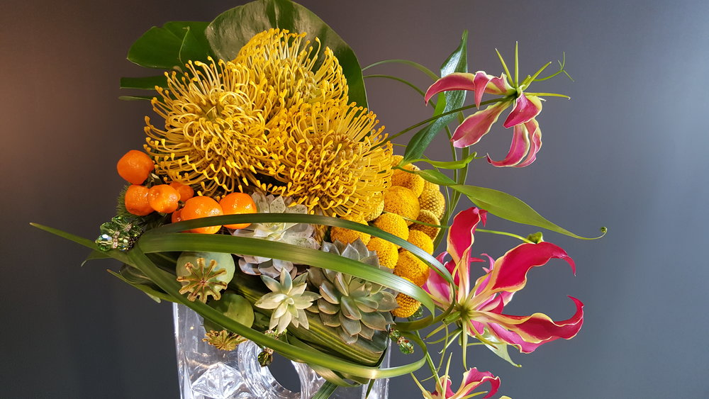 Exotic floral arrangement with unique yellow and red flowers with tangerines