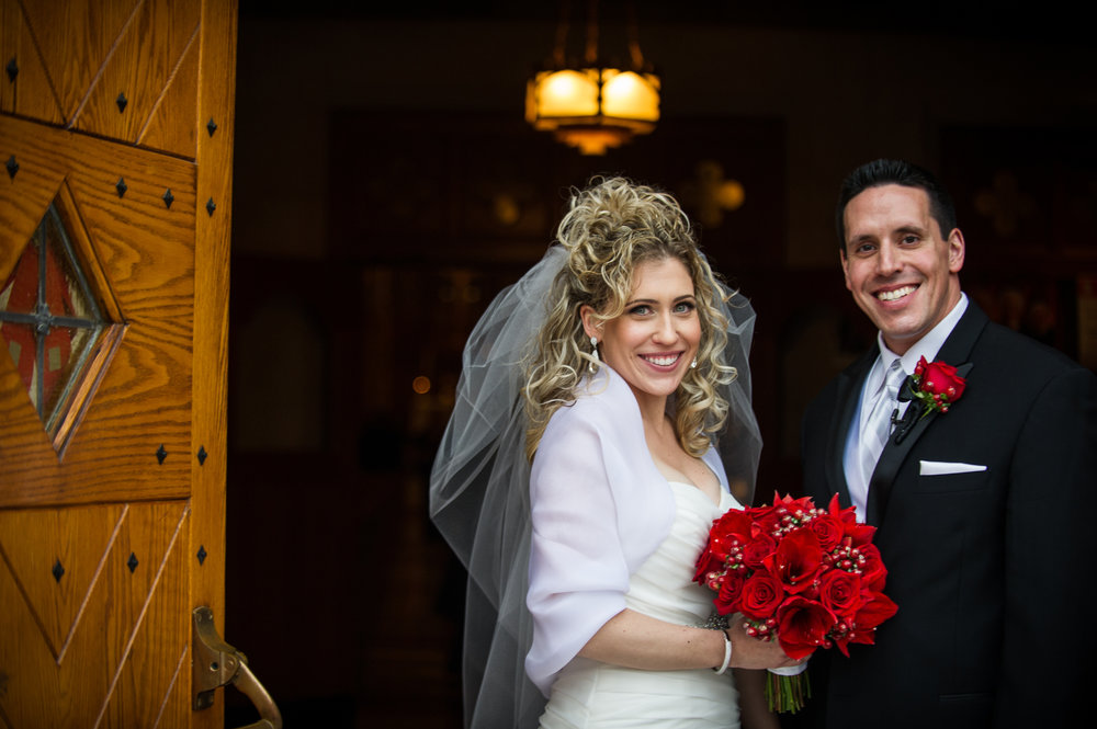 Young married couple holds beautiful bridal bouquet of red roses
