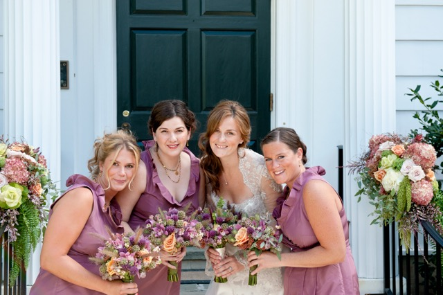 Bridesmaids and bride pose outside doorway with their beautiful bouquets
