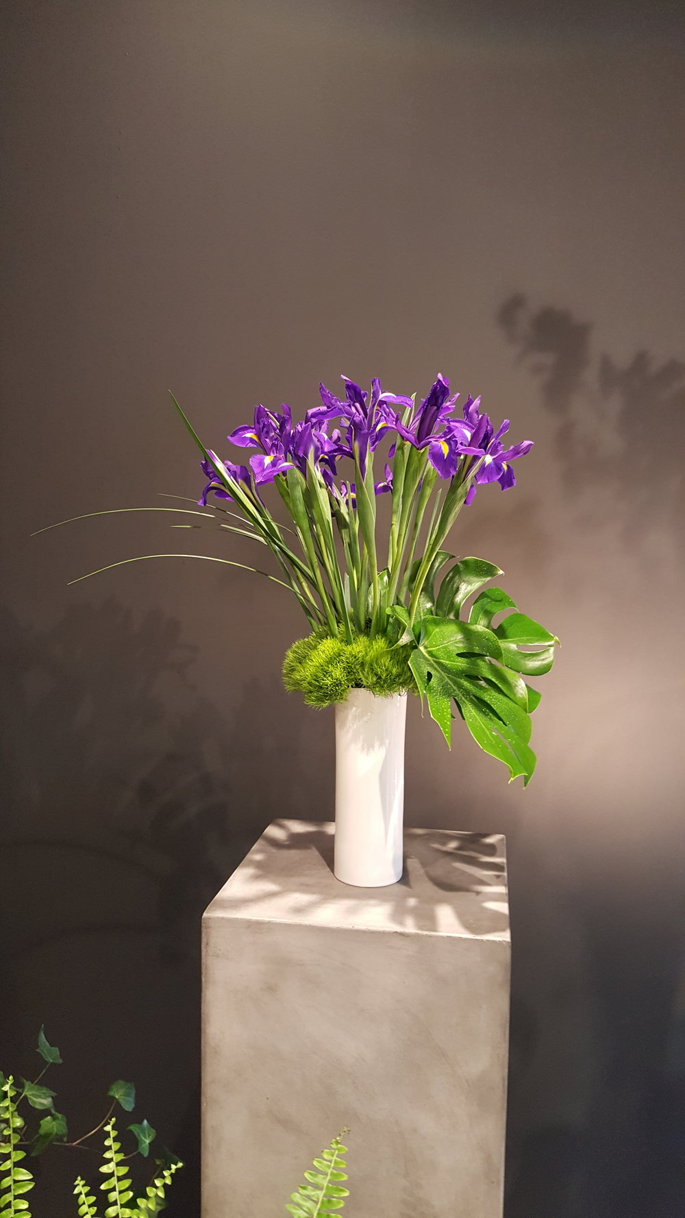 Bold purple irises in a simple vase designed by Bouquets & Beyonds