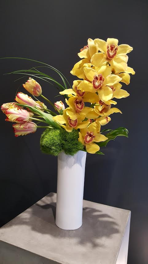Bright yellow orchids with decorative moss in a simple vase