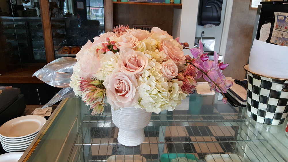 Light pink roses in simple white vase for office or restaurant decor