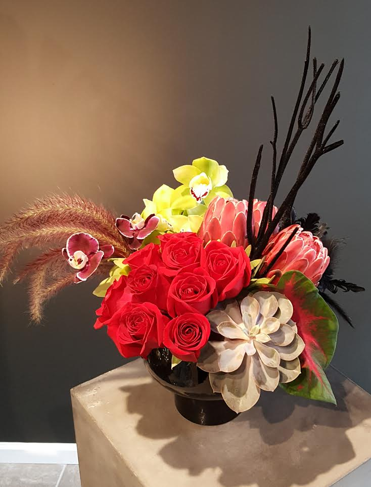 Bright vibrant roses with succulent and feather details designed by Bouquets & Beyond