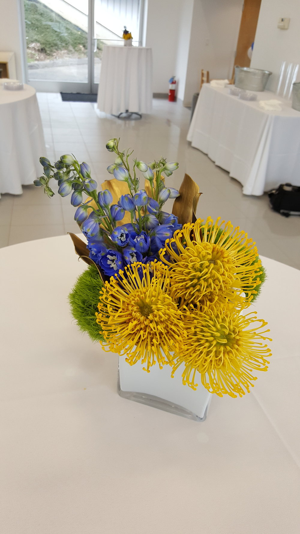Purple and yellow flowers in a short vase for corporate or restaurant decor