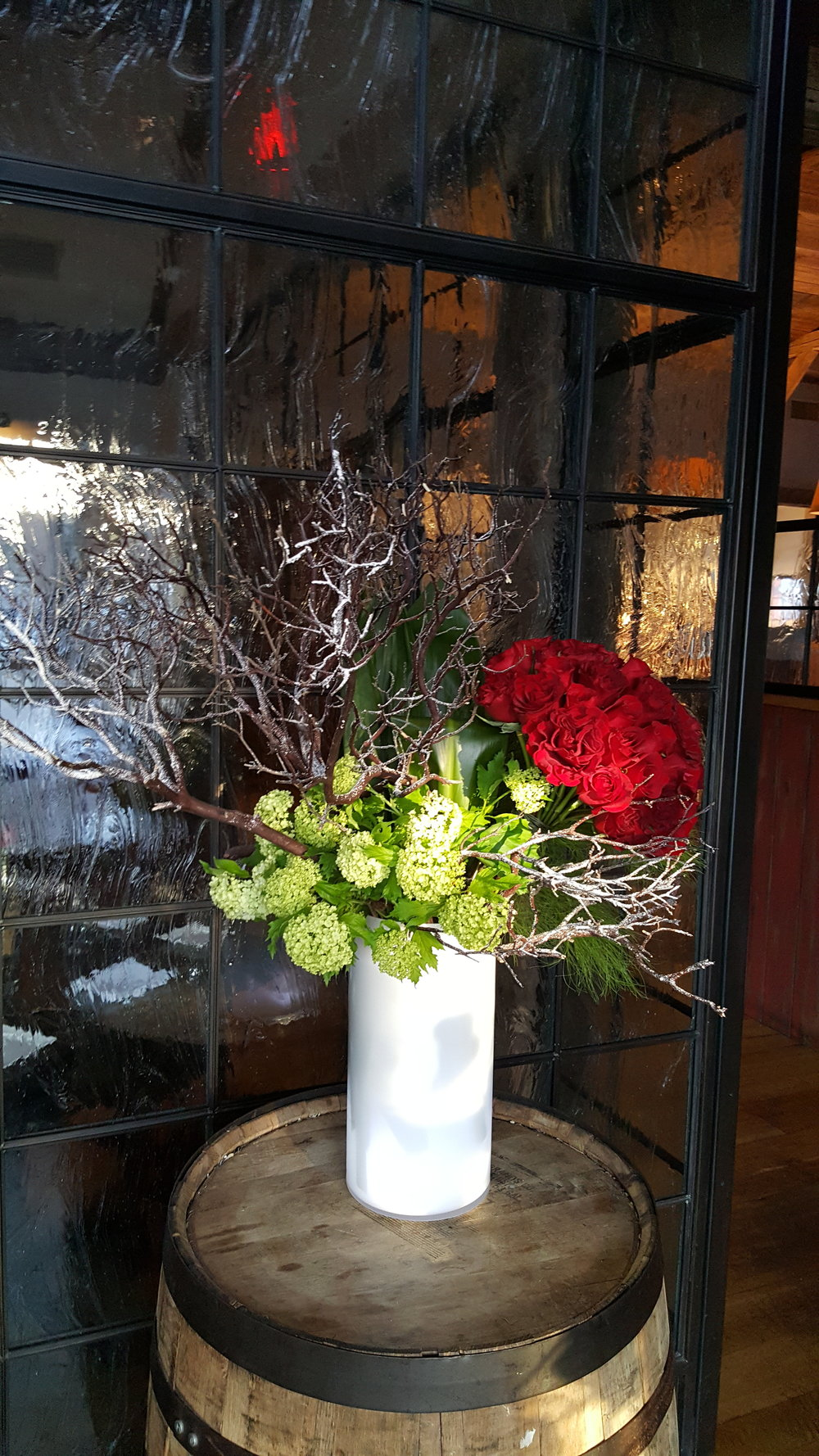 Roses, green hydrangeas and sticks in a arrangement for restaurant settings