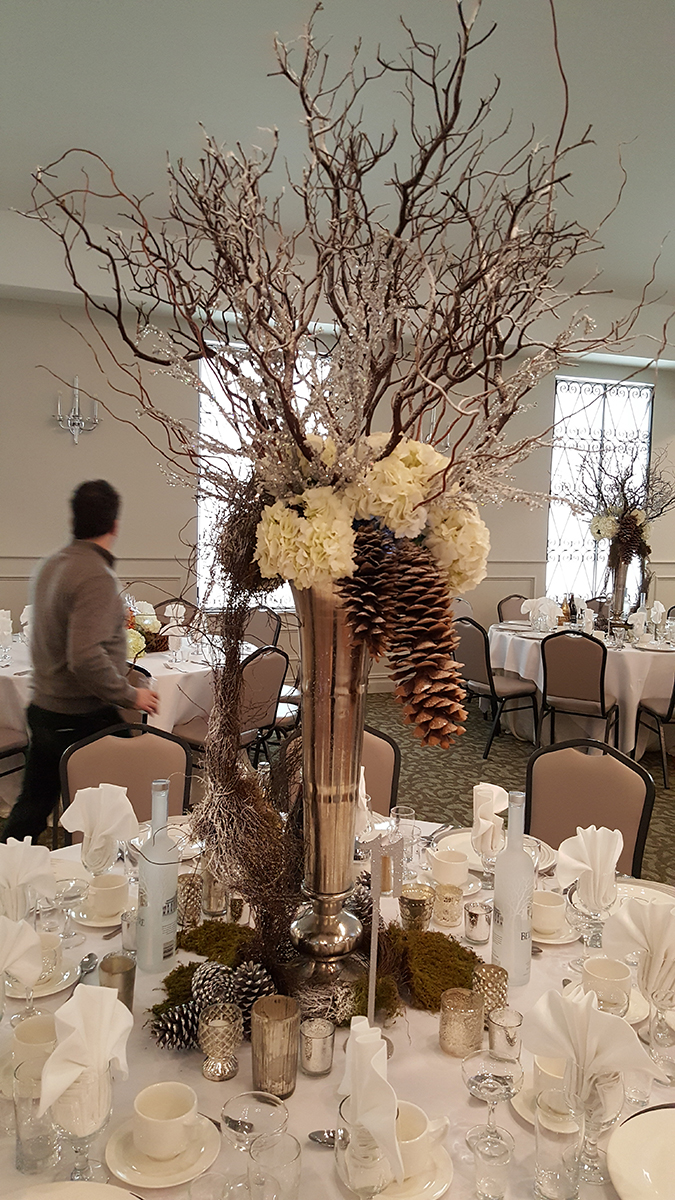 Woodsy table centerpiece with simple flowers and sticks designed by Bouquets & Beyond