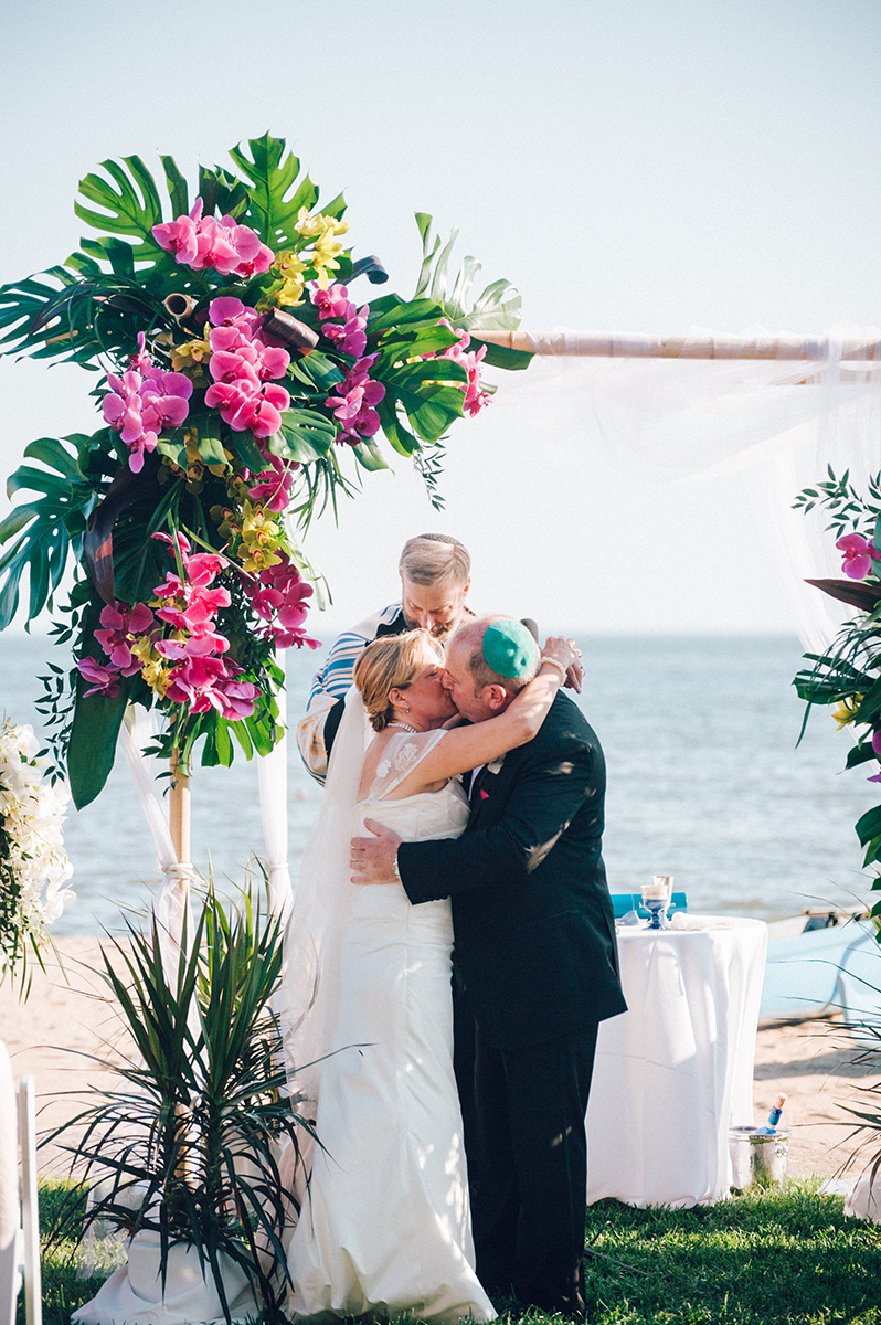 Bride and Groom kissing underneath a beautiful orchid floral arrangement