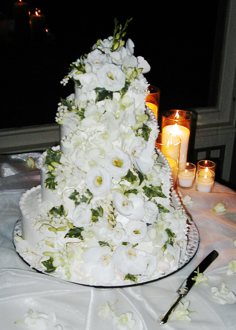 White wedding cake topped with simple white florals from Bouquets & Beyond