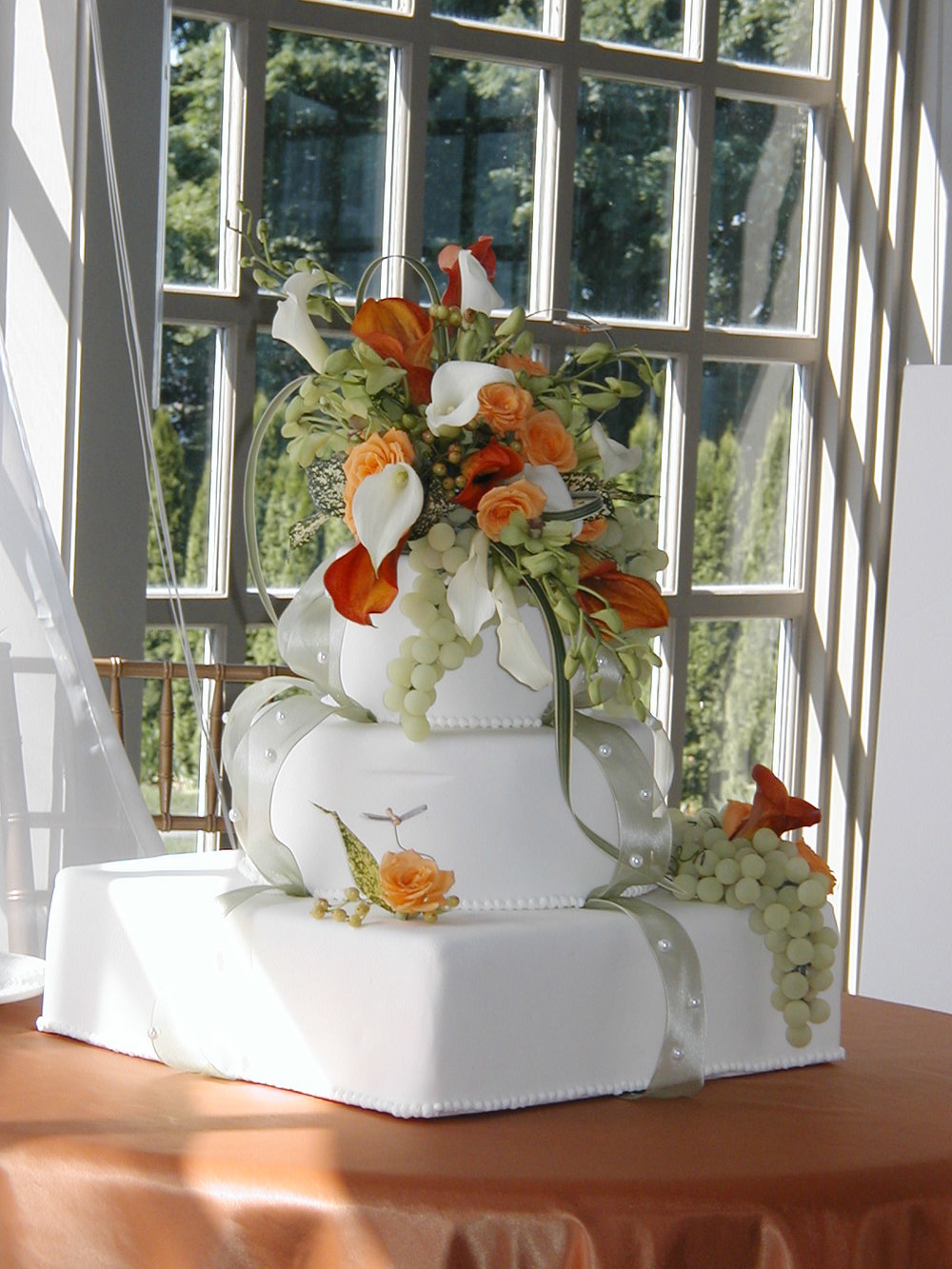 Simple white wedding cake topped with intricate flowers designed by Bouquets & Beyond