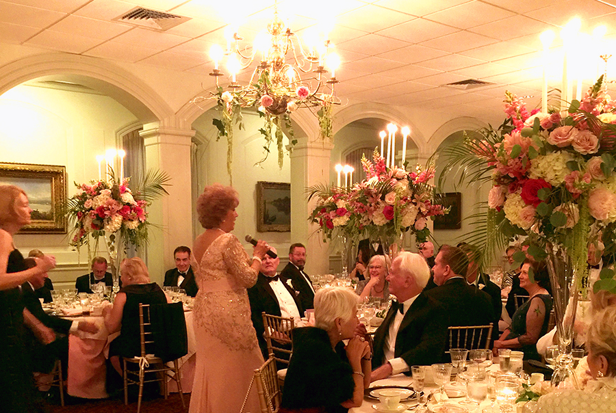 Someone giving a speech at a wedding reception surrounded by floral arrangements