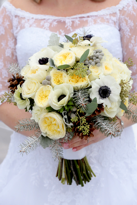 Bride holds ornate bouquet of yellow roses and more intricate flowers