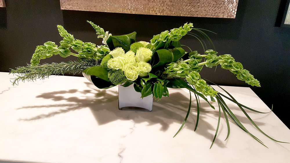 Unique green arrangement of flowers designed by Bouquets & Beyond