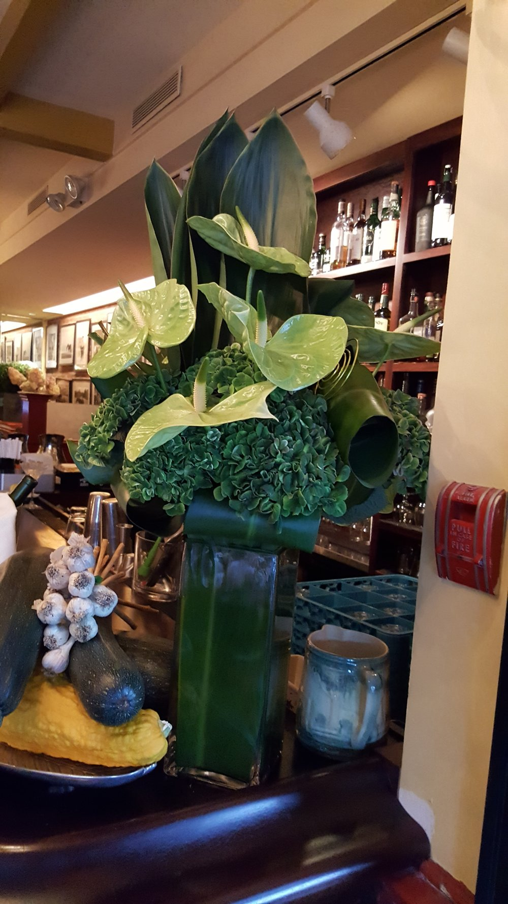 Bouquets & Beyond offers weekly floral design for offices, including this green vase of flowers on a bar