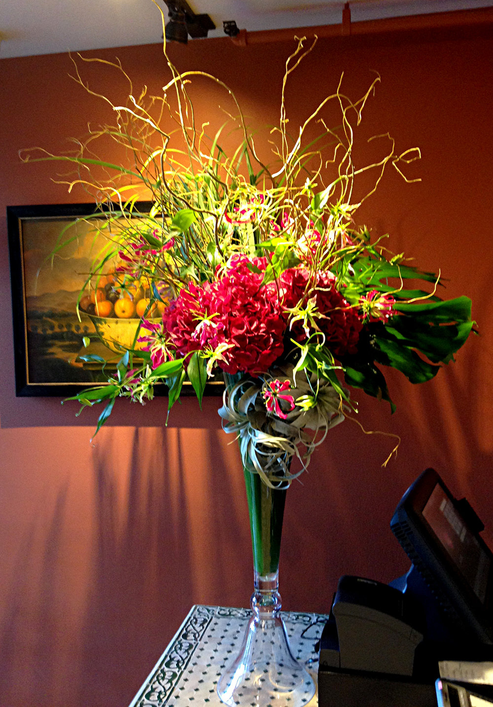 Wild grasses paired with decorative red roses designed by Bouquets & Beyond