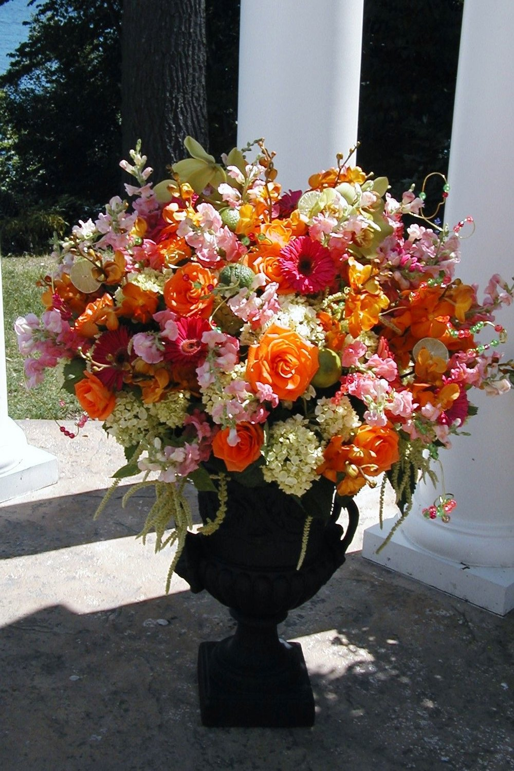 Urn overflowing with bright orange, green and purple roses for a wedding ceremony