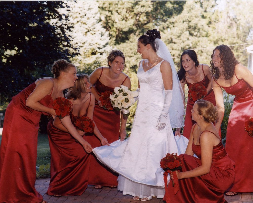 Bridesmaids in red with red bouquets of roses fawning over bride in white with white bouquet of roses