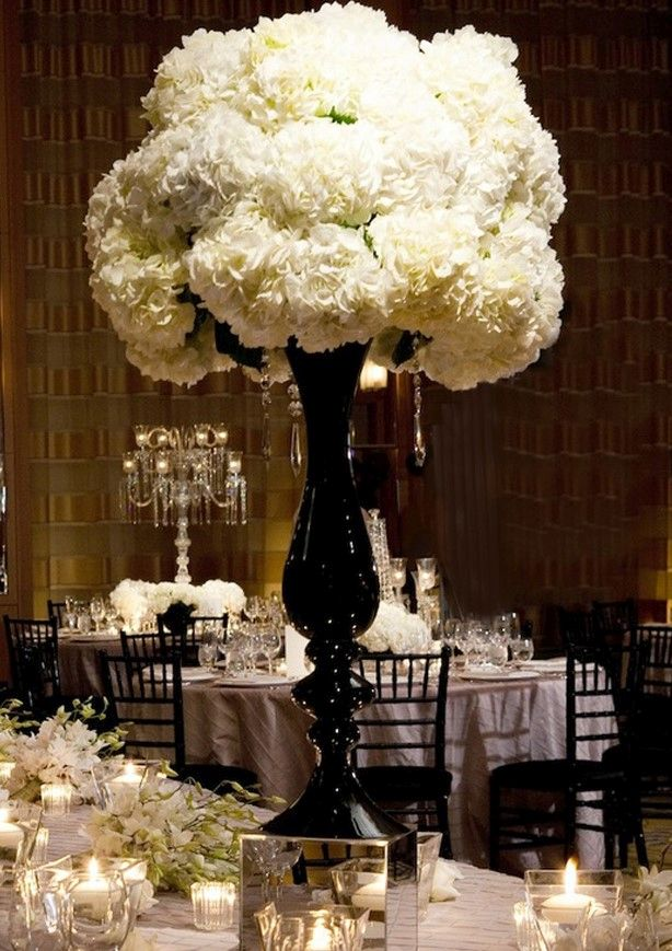 Puffy white flowers in ornate, slender urn at the center of a table