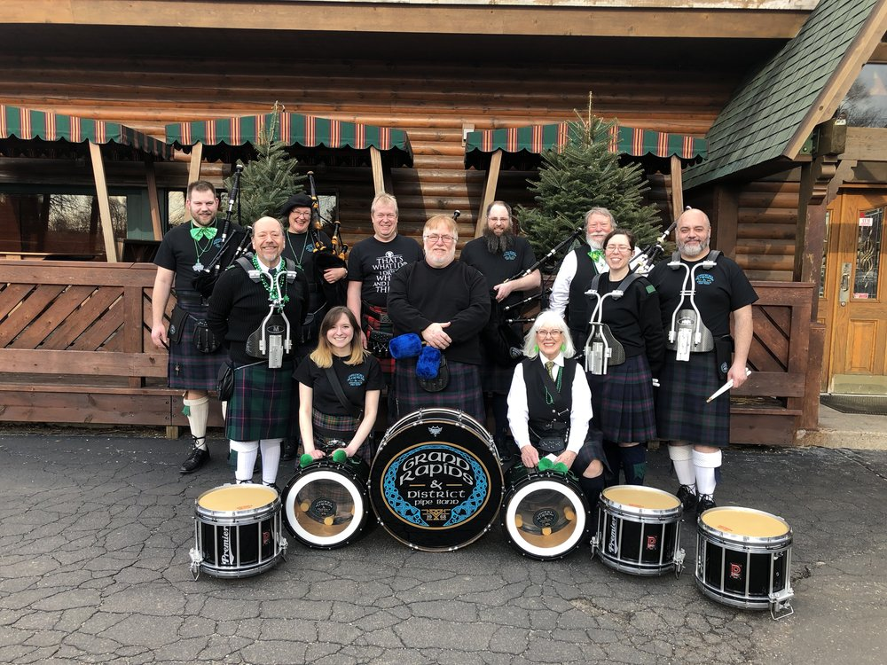 The band photo taken during the annual St. Paddy's Day pub crawl in 2019. Grand Rapids and District Pipe Band is: (Top Row from Left To Right) - Killian Smith (Piper), Melanie Redman (Piper), Rob Benson (Piper), Mike Maitner (Piper, Pipe Sargent), Fred Merritt (Piper, Piper Major) - (Middle Row from Left to Right) Scott Schaw (Snare Drummer), Brian Lewis (Bass Drummer), Elizabeth Maitner (Snare Drummer, Drum Sargent), Zach Kinney (Snare Drummer) - (Bottom Row from left to right) Celeste Neary (Tenor Drummer), Pat Merritt (Tenor Drummer)  Not Pictured - Alan Kebless (Piper), Matt Rossmiller (Snare Drummer)