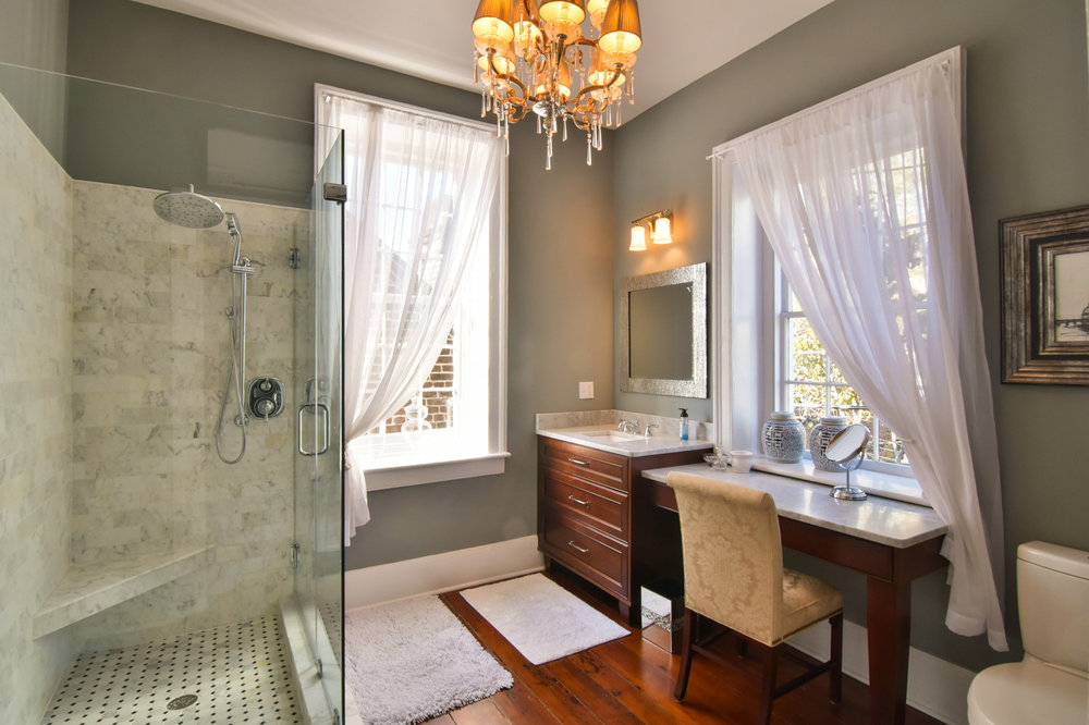 We gutted this guest bathroom, adding new flooring, a frameless glass shower, updated vanity, and painted the walls a cozy shade of green.