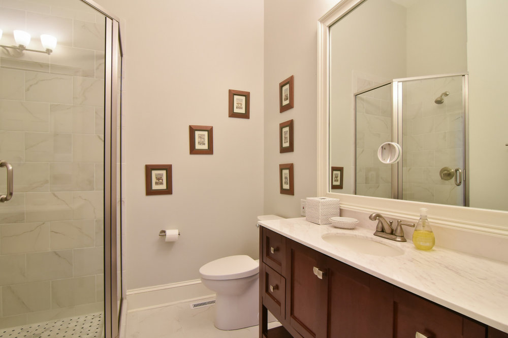 This dated bathroom needed a complete change, so we gutted the room and added new tiling, paint color, bathroom vanity, and shower.