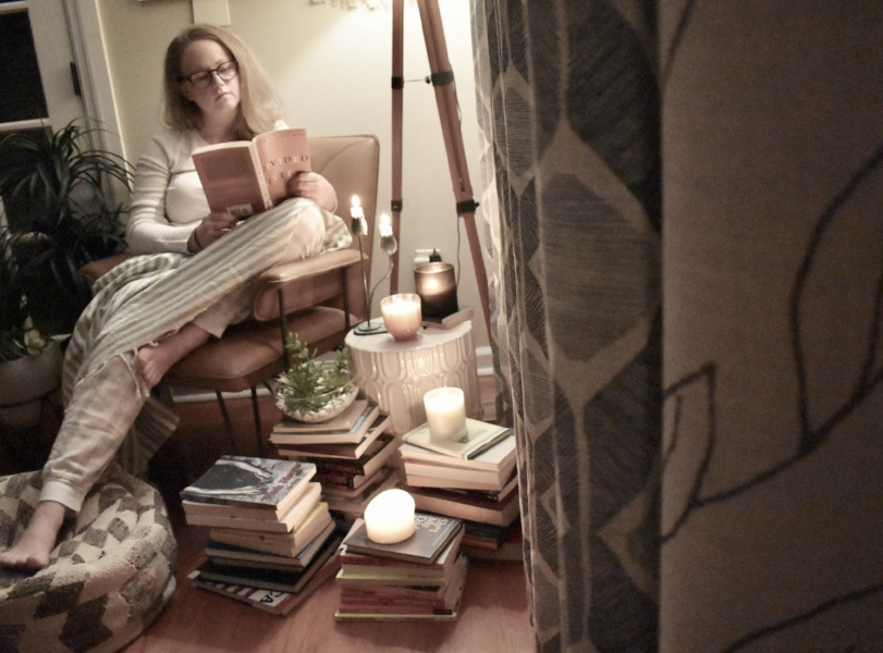 woman in chair reeding book surrounded by books and candles.jpeg