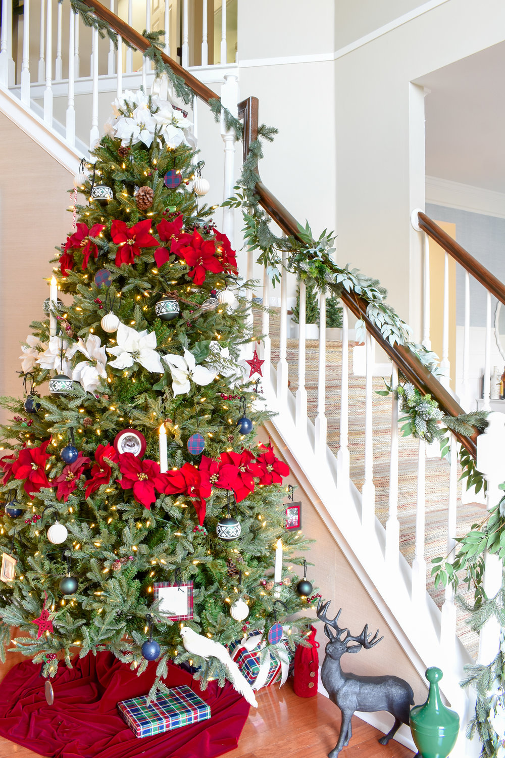 a traditional Christmas tree in the foyer adds festive cheer to a neutral space. #redandwhitechristmas #christmastree #traditionalchristmas