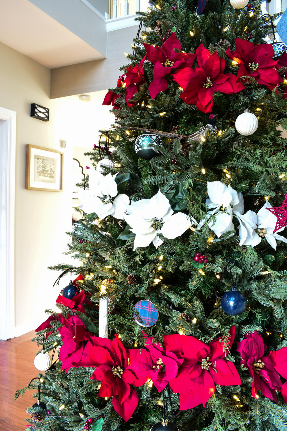 Poinsettia blooms tucked into a Christmas tree make a huge impact as a garland. You don't even have to string them! Just tuck them in a line and it'll look like a garland! #christmasdecor #traditionalchristmas #redandnavychristmas