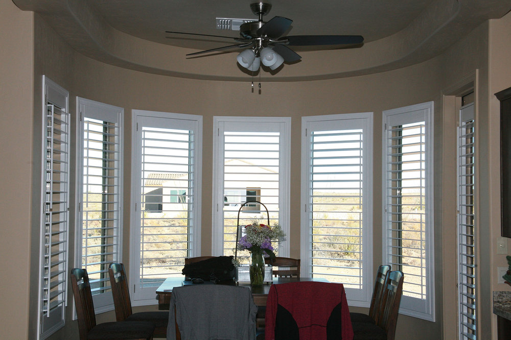 We custom fit louvered rectangular window coverings to wrap around this half-circle dining area.