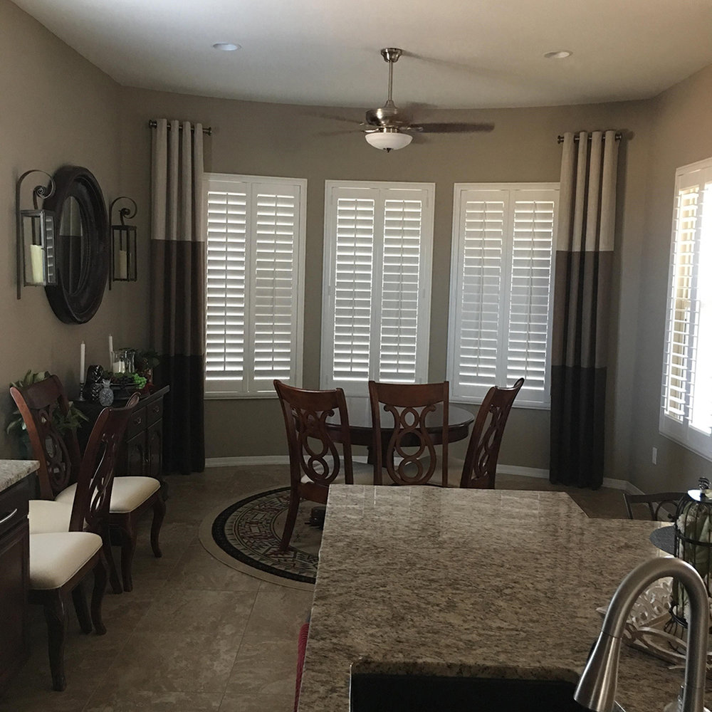 Shutters and two-tone draperies frame this dining room well.