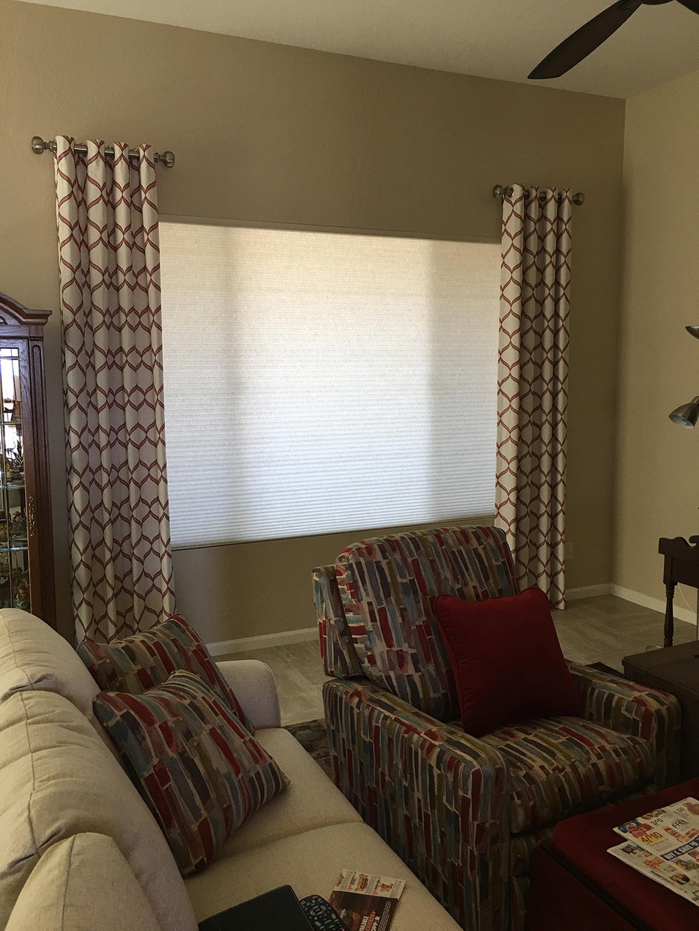 These patterned draperies enhance the look of the plain shades and add a little bit of style to the room.