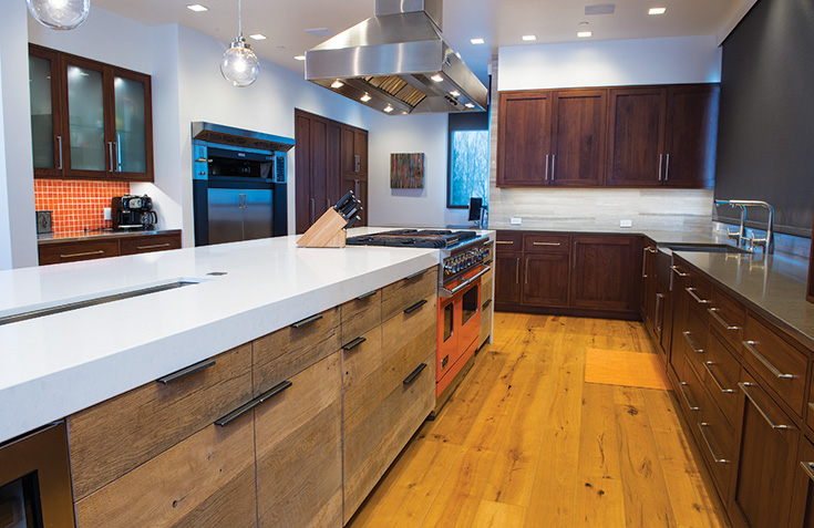 "Gorgeous Utility:  This kitchen boasts reclaimed barnwood on cabinet fronts and wood grains perfectly aligned along the large faces. The walnut, Shaker-style cabinets along the walls provide a stunning contrast in the bright room. Ching's team used a special finish on the barnwood that is water- and stain-proof, yet appears unfinished, as if ""it has just come off the barn and into the kitchen,"" he says."