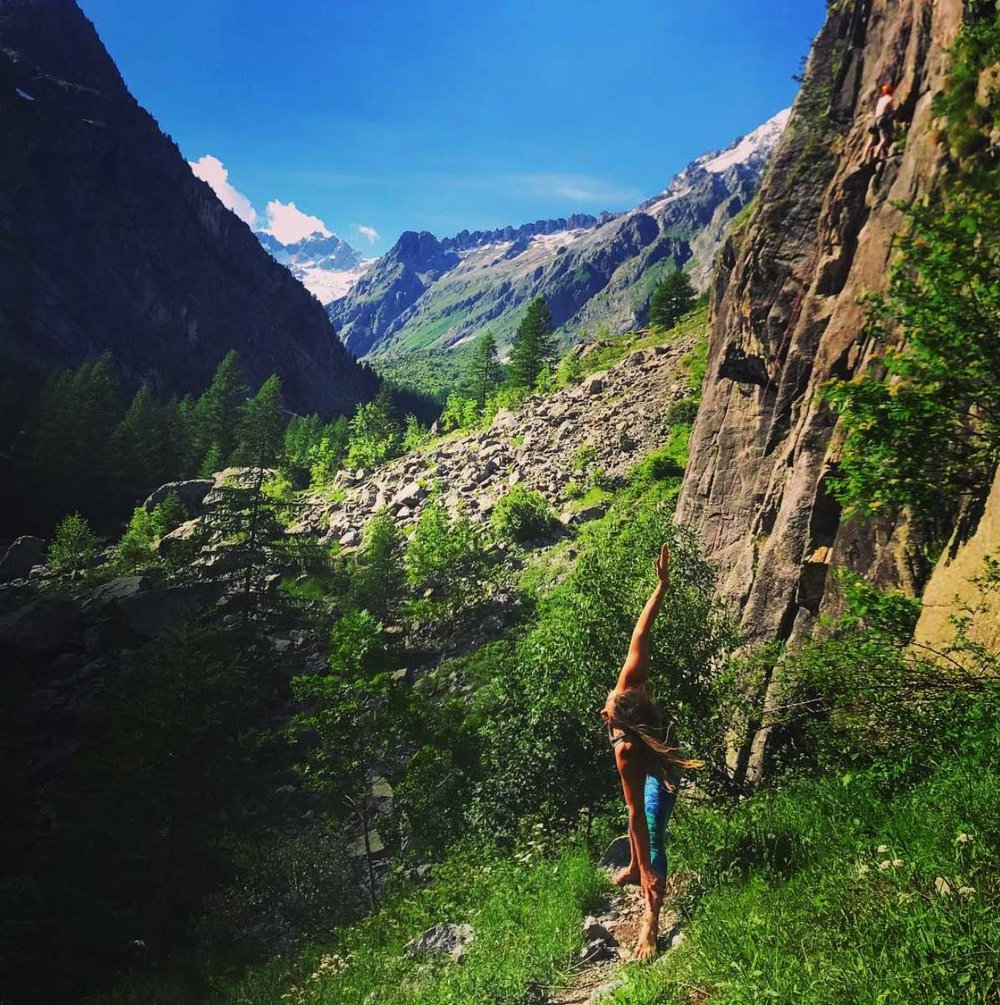 Practice yoga outdoors in a stunning environment to help warm your body for rock climbing.