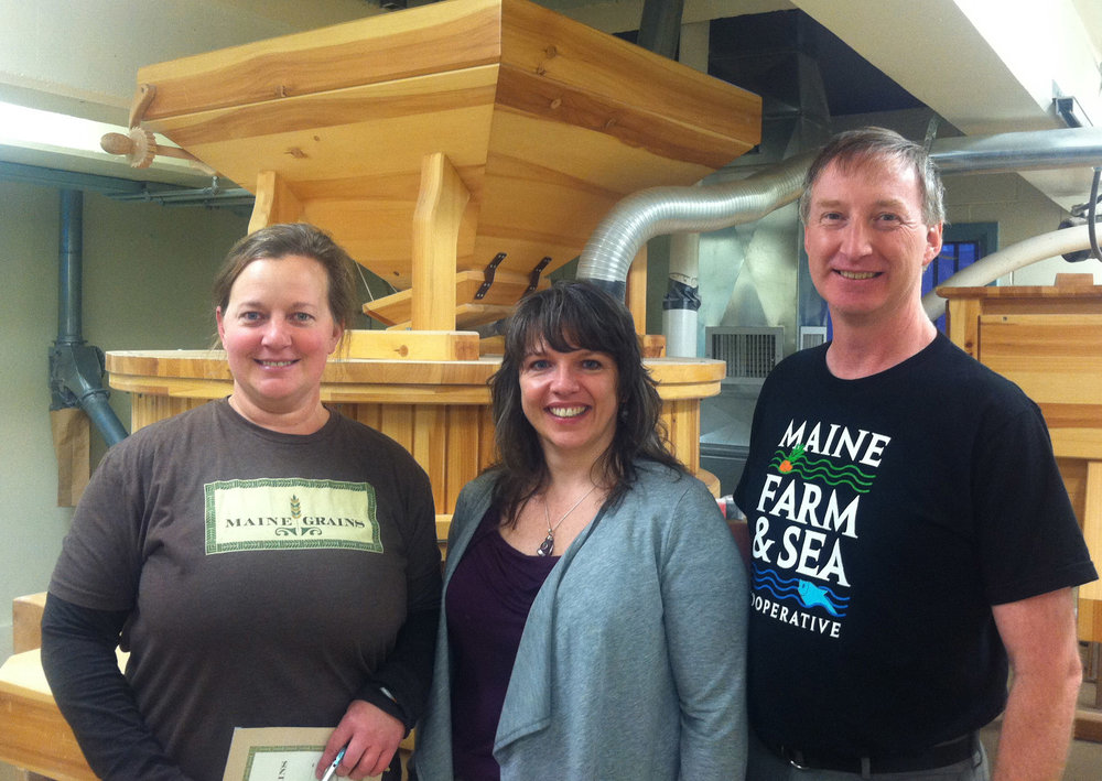 Amber Lambke, Renee Page, and Ron Adams stand inside the gristmill in Skowhegan, Maine, where Maine Grains creates traditional stone-milled flours and other products from local grains.