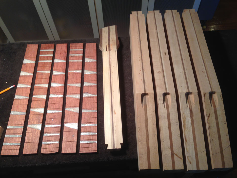 THE COMPONENTS OF SOME NECKS LAID OUT ON THE BENCH: FRETBOARDS, A PARTIALLY-SHAPED NECK, AND ROUGH LAMINATED NECK BLOCKS THAT HAVEN'T BEEN TRIMMED OR SHAPED YET.
