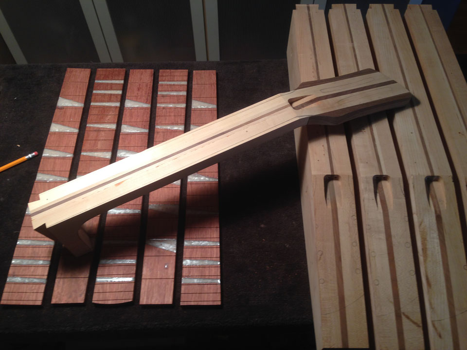 NECK COMPONENTS: ROUGH FRETBOARDS AND ROUGH-TRIMMED LAMINATED NECK BLOCKS. A PARTIALLY-TRIMMED NECK IS SHOWN, CENTER.