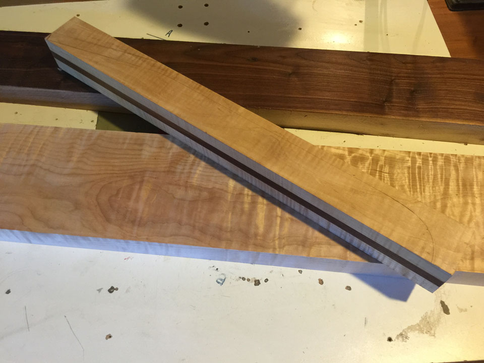 A NECK BLANK IS LAMINATED FROM TWO HARD MAPLE STRIPS WITH A HARD WALNUT CENTER STRINGER.