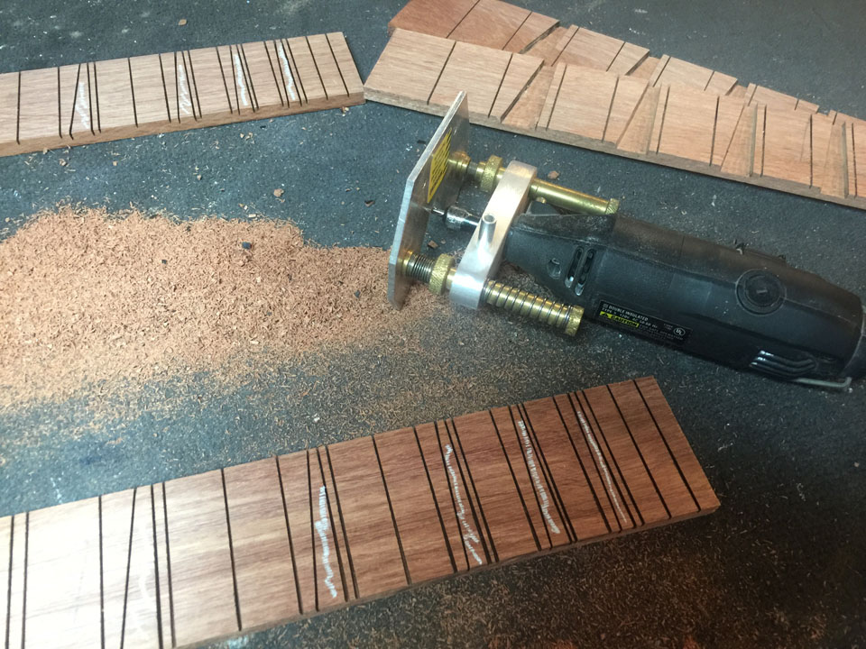 FRET SLOTS ARE CUT WITH A SPECIAL SAW, THEN THE SIDES OF THE TRIANGULAR FRET MARKERS ARE SLOTTED. THE FRET MARKER AREAS ARE CUT OUT BY HAND WITH A MINIATURE ROUTER.