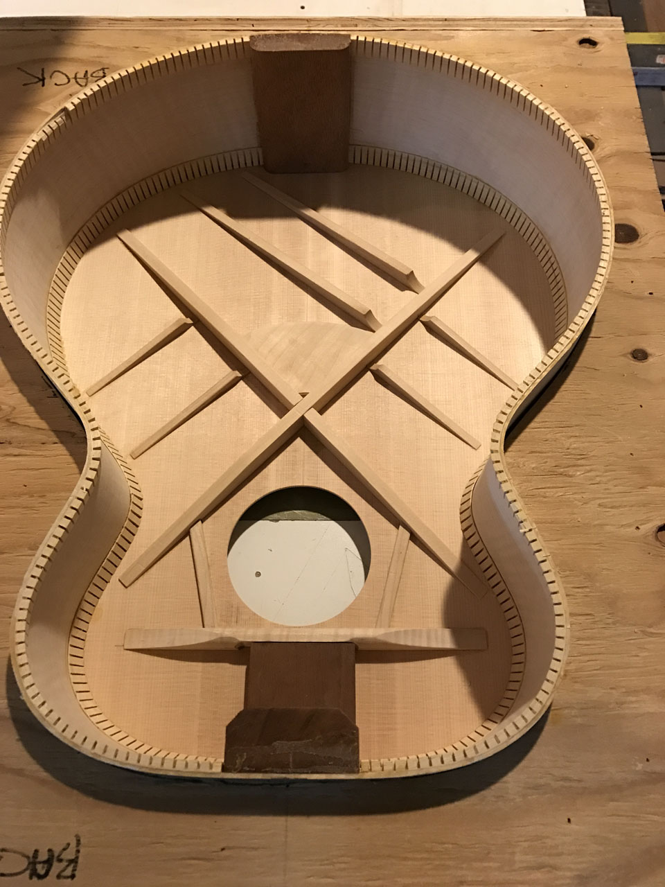 "LOOKING AT THE INSIDE OF A JUMBO BODY WITH THE TOP GLUED INTO PLACE. BRIDGE PLATE HAS BEEN FITTED BELOW THE ""X"" BRACE. SOUND HOLE ON THIS ONE HAS NOT BEEN BOUND YET."