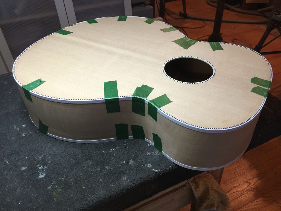 "WHITE BINDING BEING GLUED TO THE ""BLUEBURST"" SOUND SAMPLE 700C JUMBO BODY."